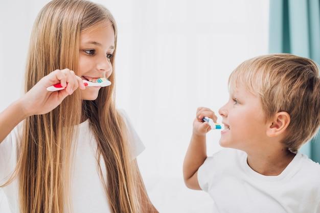 Irmãos escovando os dentes Foto gratuita