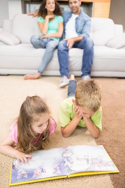 Irmãos felizes deitado no tapete lendo um livro de histórias Foto Premium