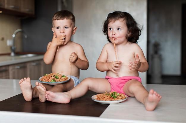Irmãos jovens bonitos comendo macarrão Foto gratuita