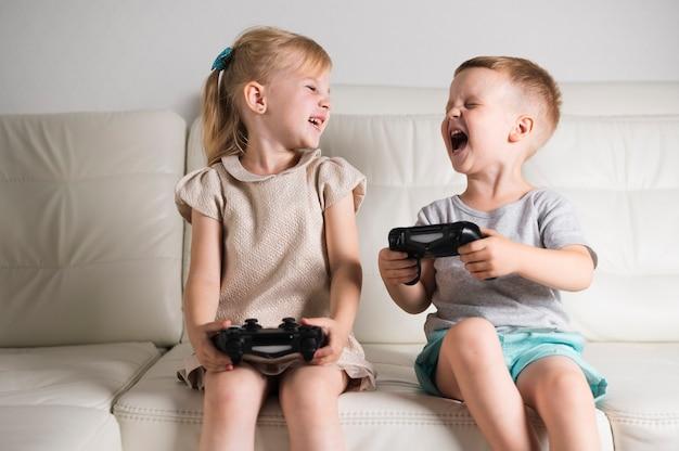 Irmãos pequenos jogando jogos digitais com joystick Foto gratuita