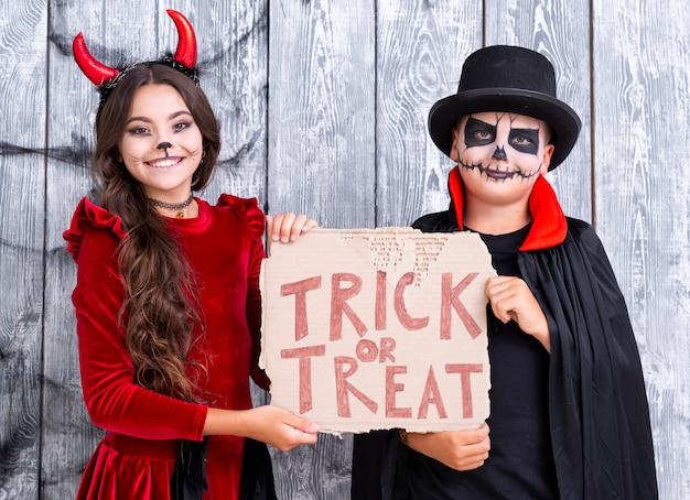 Irmãos segurando doces ou travessuras cadastre-se em trajes de halloween Foto gratuita