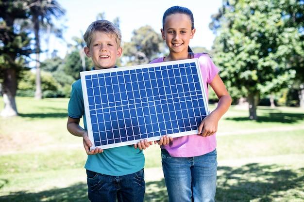 Irmãos segurando um painel solar Foto Premium