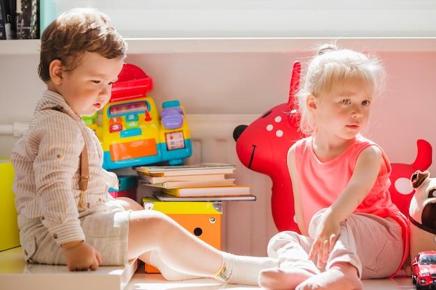 Irmãos sentados com brinquedos posando Foto gratuita