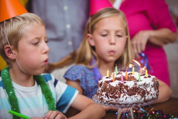 Irmãos soprando velas de aniversário Foto Premium