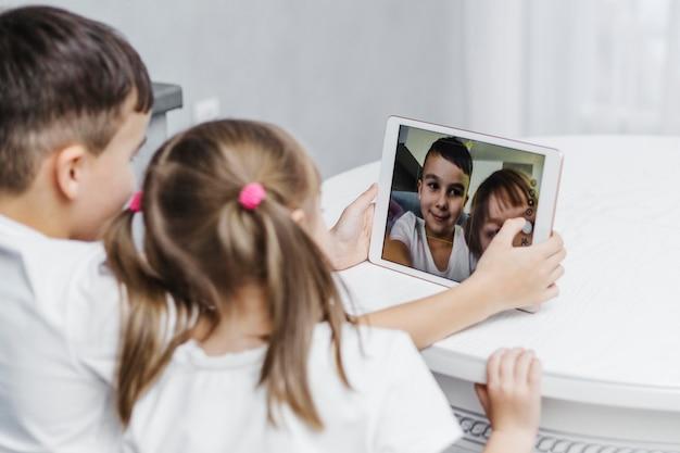 Irmãos tirando um autorretrato em tablet digital Foto gratuita
