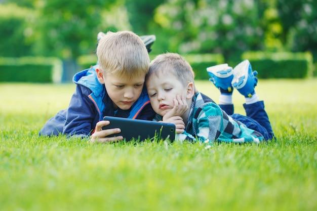 Irmãos, usando, um, tabuleta, yingon, capim, parque, em, suny, dia Foto Premium