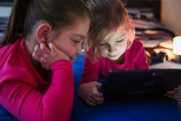 Irmãs assistindo vídeo na mesa Foto gratuita