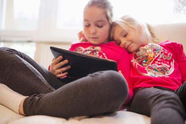 Irmãs bonitos assistindo vídeo no tablet Foto gratuita