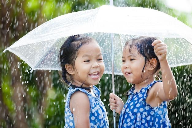 Irmãs com guarda-chuva se divertindo brincando na chuva Foto Premium