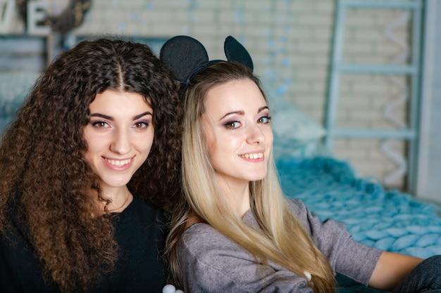 Irmãs de cabelo preto e cabelos louros sentar em uma manta de malha azul juntos na cama. Foto Premium