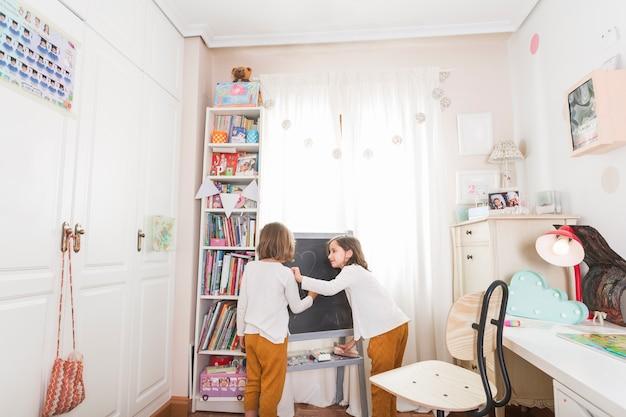 Irmãs de desenho no quadro-negro Foto gratuita