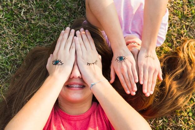 Irmãs deitado na grama verde, cobrindo os olhos com tatuagens na palma da mão Foto gratuita