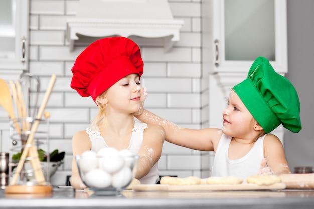 Irmãs em chapéus de cozinheiro brilhante assando juntos em uma cozinha Foto Premium