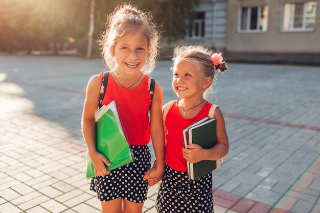 Irmãs felizes vestindo mochilas e segurando livros Foto Premium