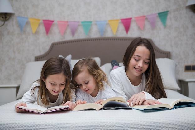 Irmãs lendo livro juntos Foto gratuita