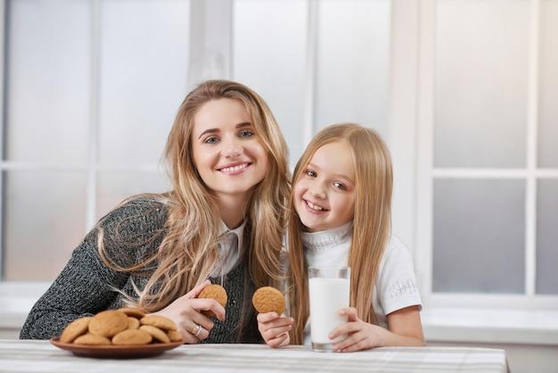 Irmãs mais velhas e mais jovens comendo biscoitos e sorriso Foto Premium