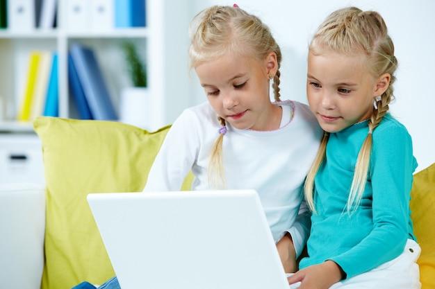 Irmãs que usam o portátil Foto gratuita