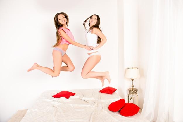 Irmãs sexy de pijama pulando na cama e de mãos dadas Foto Premium