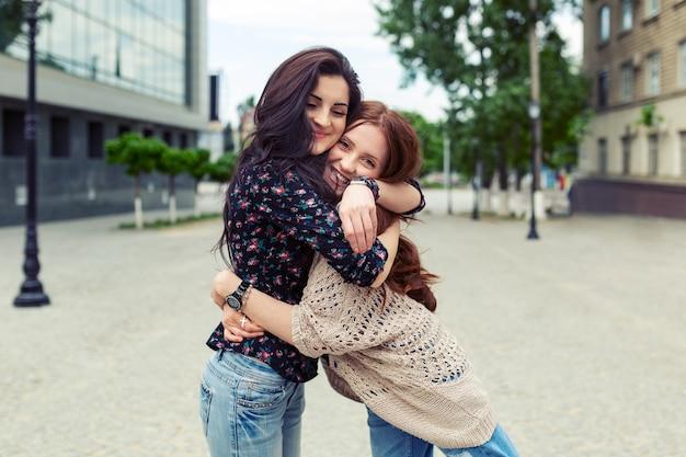 Irmãs sorridentes despreocupadas, abraçando e se divertindo juntos Foto gratuita