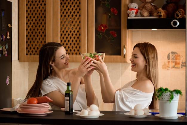 Irmãs sorridentes preparando o jantar juntos na cozinha Foto Premium