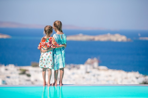 Irmãzinhas adoráveis na praia durante as férias de verão Foto Premium