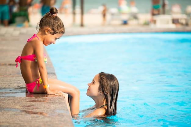 Irmãzinhas nadar na piscina Foto Premium
