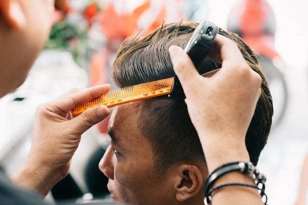 Irreconhecível, cabeleireiro masculino, cortar o cabelo do cliente com aparador e pente Foto gratuita