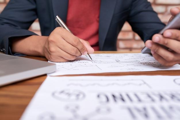 Irreconhecível homem sentado à mesa com smartphone e desenho diagrama comercial no papel Foto gratuita