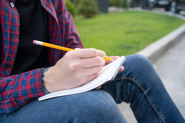 Irreconhecível homem sentado na calçada da estrada e escrevendo na nota Foto gratuita
