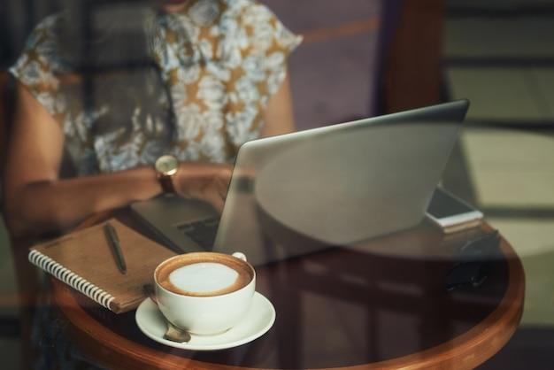 Irreconhecível jovem sentado à mesa no café e trabalhando no laptop Foto gratuita