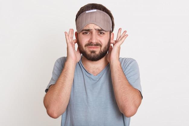 Irritado jovem revoltado com barba, olhando diretamente cobrindo seus ouvidos com os dedos, vestindo camiseta e máscara de dormir Foto gratuita