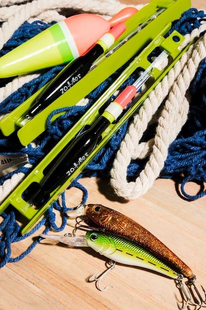 Isca de pesca; linha de pesca e flutuador de pesca na superfície de madeira Foto gratuita