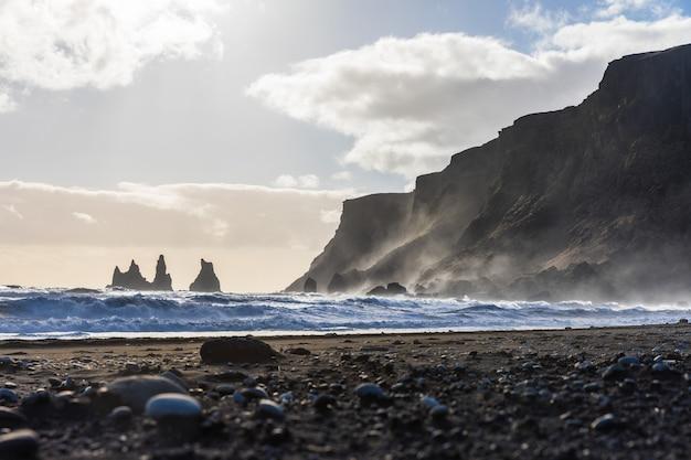 Islândia, vik praia negra com ondas e rochas Foto Premium