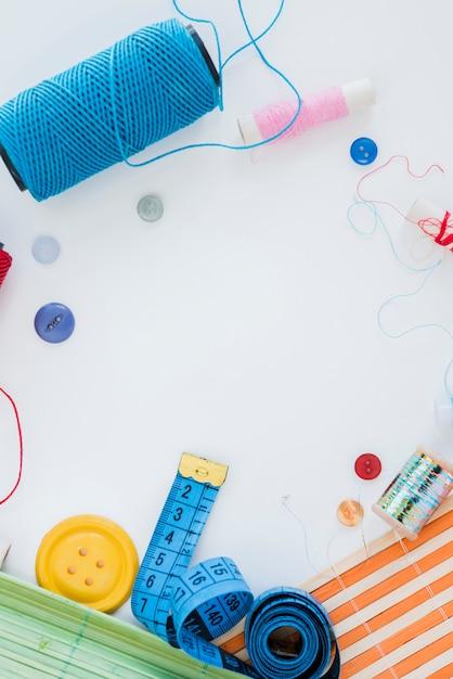 Itens de costura layout na mesa branca Foto gratuita