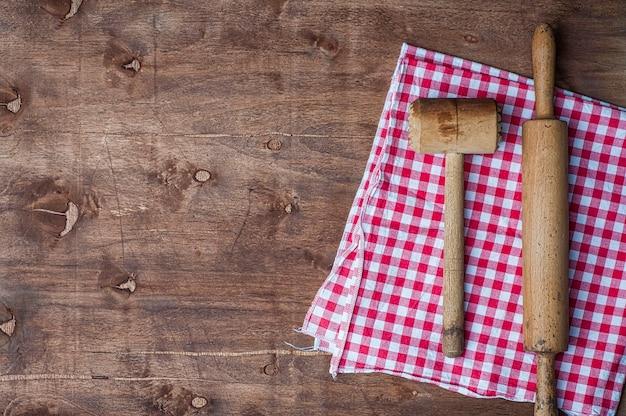Itens de cozinha em madeira em um guardanapo vermelho, rolo e martelo para bater carne Foto Premium