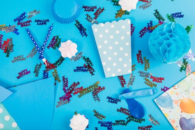 Itens de festa e zéfiros em fundo azul Foto gratuita