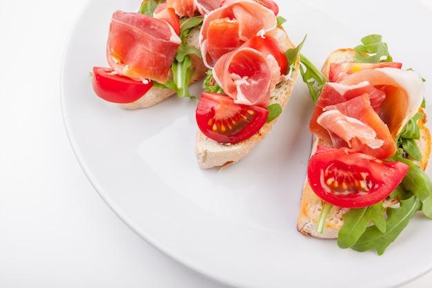Jamon. fatias de pão com presunto serrano espanhol servido como tapas. presunto, aperitivo espanhol. presunto isolado no fundo branco Foto Premium