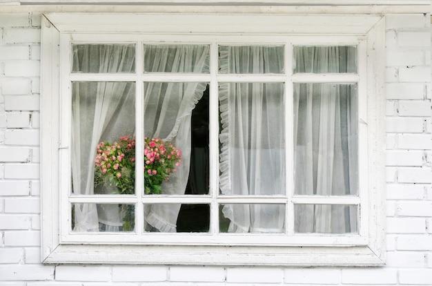 Janela branca com cortinas, um buquê de flores no parapeito da janela Foto Premium