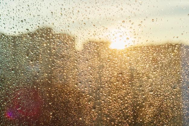 Janela ensolarada de fundo com gotas de chuva brilhante, vista da cidade moderna Foto Premium