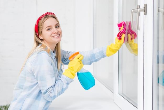 Janelas de limpeza de mulher sorridente Foto gratuita