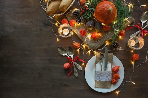 Jantar de ação de graças. jantar de halloween. mesa festiva com abóbora, folhas de outono e decoração sazonal de outono. Foto Premium