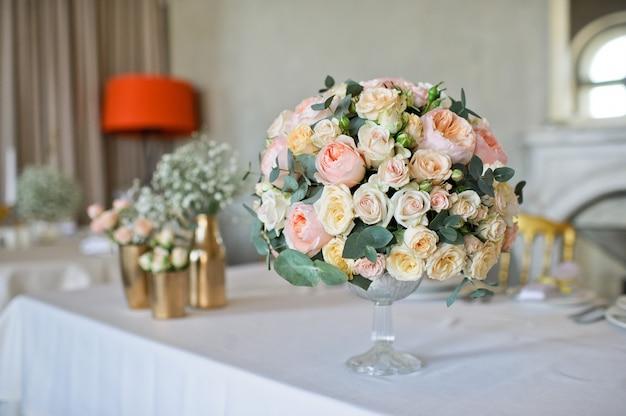 Jantar de casamento no restaurante, mesas decoradas com vasos de rosas. Foto Premium