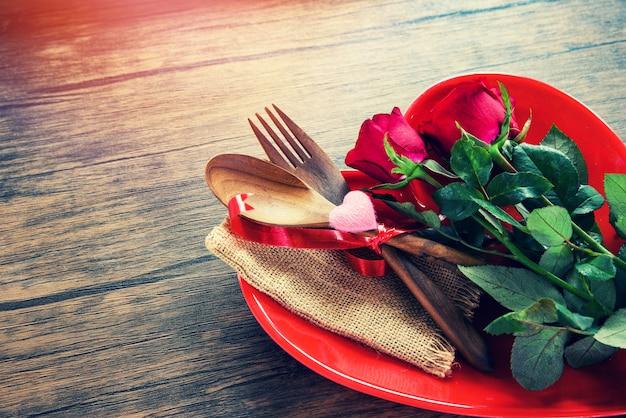 Jantar de dia dos namorados romântico amor comida e amor cozinhando ajuste de mesa romântico decorado com madeira garfo colher rosas em coração vermelho placa Foto Premium