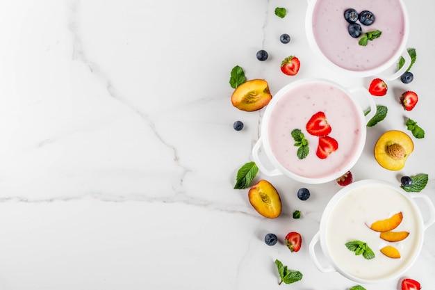 Jantar de dieta saudável de verão, comida vegetariana, sobremesa, várias sopas cremosas doces de frutas e bagas Foto Premium