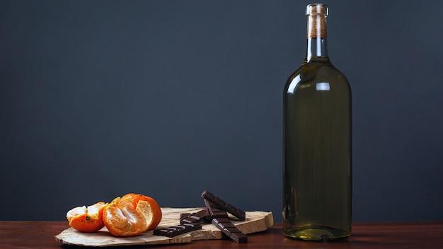 Jantar romântico. garrafa de vinho com chocolates doces e tangerinas em um fundo escuro. Foto Premium