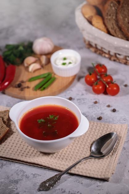 Jantar saboroso e saudável. um prato com sopa de beterraba em cima da mesa, ao lado do tabuleiro, inclui legumes, salsa, endro, cebola verde, alho, pimenta, tomate cereja e pão. Foto Premium