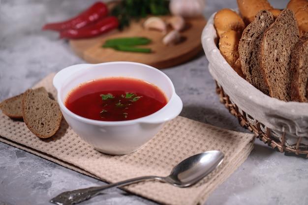 Jantar saboroso e saudável. um prato com sopa de beterraba na mesa, ao lado do tabuleiro, é salsa, endro, cebola verde, alho, pimenta e uma cesta com pão. Foto Premium