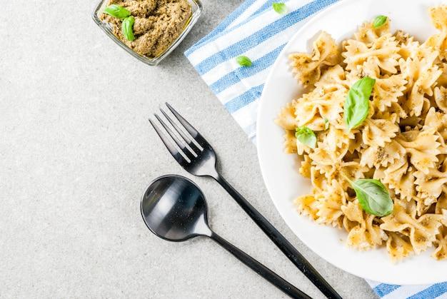 Jantar vegano. massa farfalle com molho pesto e folhas de manjericão Foto Premium