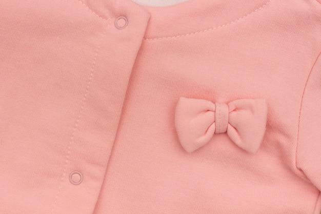Jaqueta elegante rosa de parte menina com close-up de proa, textura de fundo Foto Premium