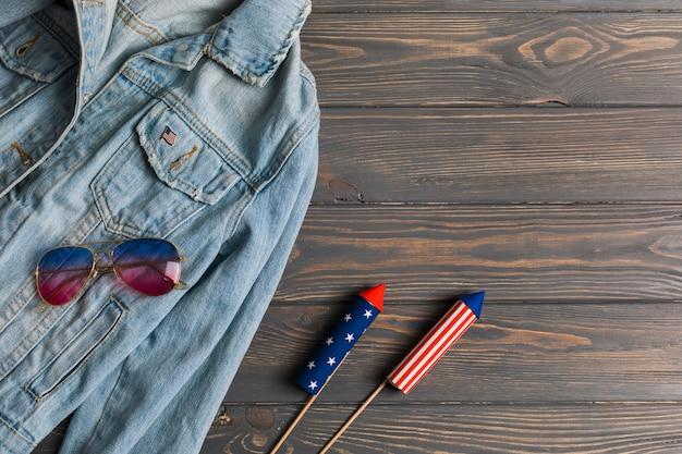Jaqueta, óculos escuros e fogos de artifício na mesa Foto gratuita